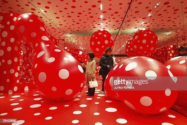 Visitors walk through the 'Kusamatrix' exhibition by artist Kusama Yayoi at Roppongi Hills February 8 2004 in Tokyo Japan The trademark of Kusama's...