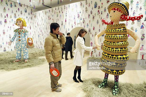 Visitors walk through the Kusamatrix exhibition by artist Kusama Yayoi at Roppongi Hills February 8 2004 in Tokyo Japan The trademark of Kusama's...