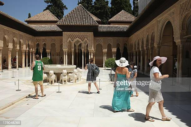 Visitors walk through the Patio of the Lions in the Nasrid Palaces at the Alhambra on July 23 2013 in Granada Spain Southern Spain is among Europe's...