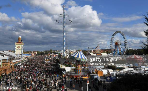 Visitors walk through the Theresienwiese fairground of the Oktoberfest beer festival in Munich, southern Germany, on October 3, 2019. - The world's...