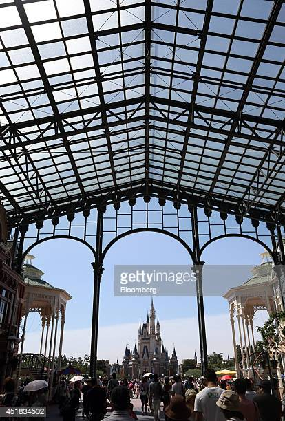 Visitors walk towards the Cinderella Castle at Tokyo Disneyland operated by Oriental Land Co in Urayasu Chiba Prefecture Japan on Tuesday July 8 2014...