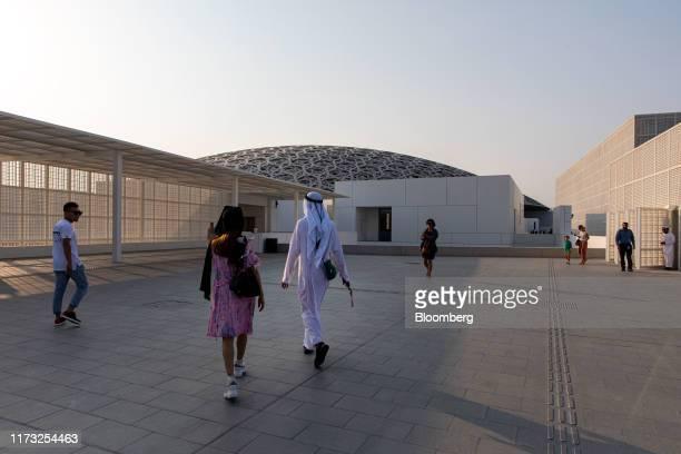 Visitors walk towards the entrance of the Louvre Abu Dhabi museum on Saadiyat Island in Abu Dhabi, United Arab Emirates, on Wednesday, Oct. 2, 2019....