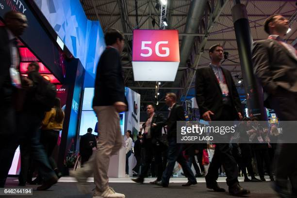 Visitors walk under a 5G logo hanging from the ceiling on the second day of the Mobile World Congress on February 28 2017 in Barcelona Phone makers...