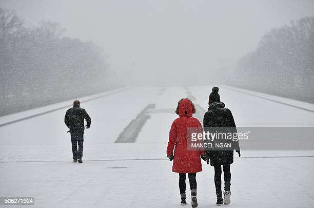 Visitors walk under snowfall infront of the Lincoln Memorial on January 22 2016 in Washington DC Thousands of flights were cancelled and supermarket...