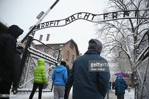 Visitors walk under the infamous 'Arbeit Macht Frei' slogan which literally translates to 'Work Makes Free' at the former Auschwitz I concentration...