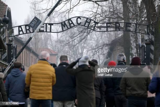 Visitors walk under the notorious Work Makes One Free inscription at the entrance to the Auschwitz I memorial concentration camp site on February 15...