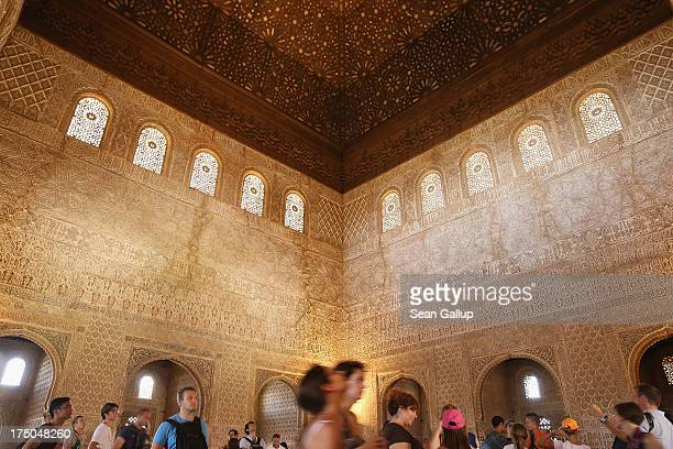 Visitors walk under the ornate ceiling of the Hall of the Ambassadors in the Nasrid Palaces at the Alhambra on July 23 2013 in Granada Spain Southern...