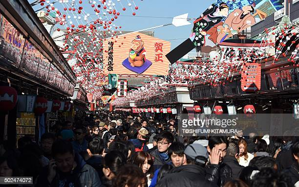 Visitors walk underneath New Year's Day decorations celebrating next year's 'Year of the Monkey' from the Chinese zodiac at the Nakamise shopping...