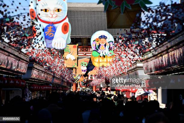 Visitors walk underneath New Year's Day decorations celebrating next year's 'Year of the Dog' from the Chinese zodiac at the Nakamise shopping alley...