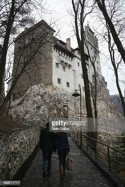 Visitors walk up to Bran Castle famous as 'Dracula's Castle' on March 10 2013 in Bran Romania Bran Castle's reputation as the supposed home to...