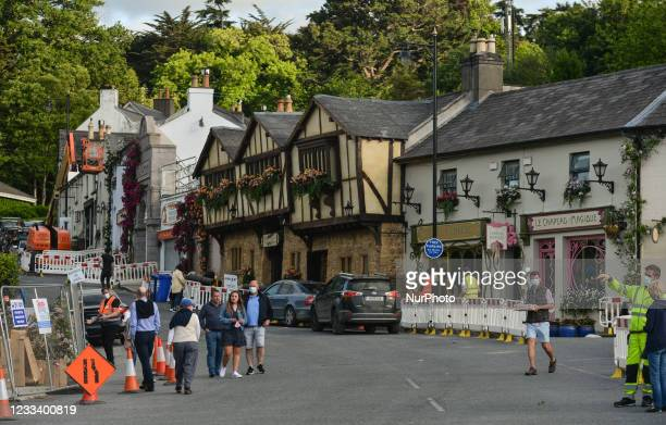 Visitors walking around the main street with trannsformed houses decorated with flowers in the village of Enniskerry in County Wicklow. There are...
