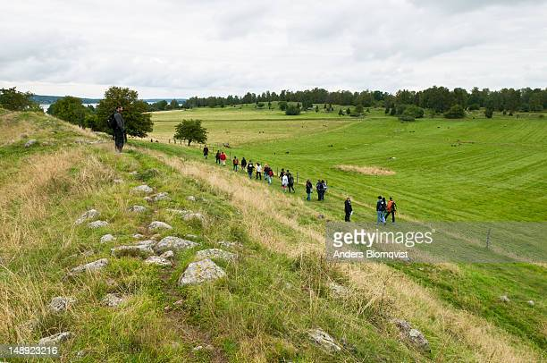 Visitors walking on 'The Black Earth', a field where a Viking village once stood, Birka.
