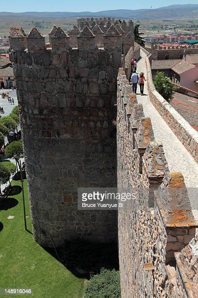 Visitors walking on top of medieval city wall.