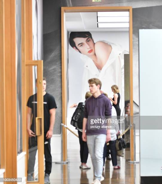 Visitors walking past photographs by Mario Testino during a press event at the Museum fuer Fotografie in Berlin Germany 1 June 2017 Three new...