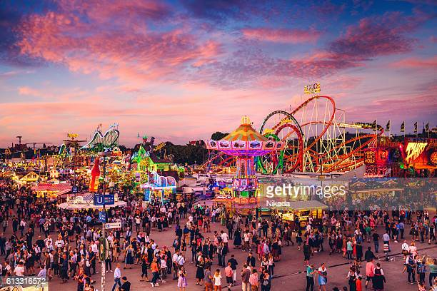 visitors walking through oktoberfest fairgrounds, munich, germany - carnival stock photos and pictures