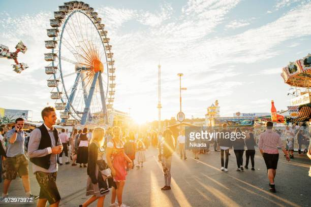 visitors walking through oktoberfest fairgrounds, munich, germany - ferris wheel stock pictures, royalty-free photos & images
