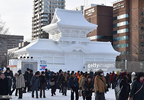 Visitors walks past a large snow sculpture of the Kasuga Grand Shrine during the 66th annual Sapporo Snow Festival on February 5 2015 The weeklong...