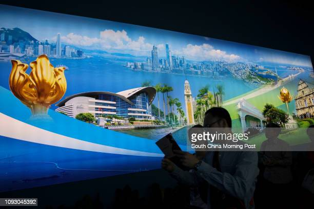 Visitors walks past a panorama picture of Hong kong and Macau at a special exhibition celebrating the achievements in the past five years since the...