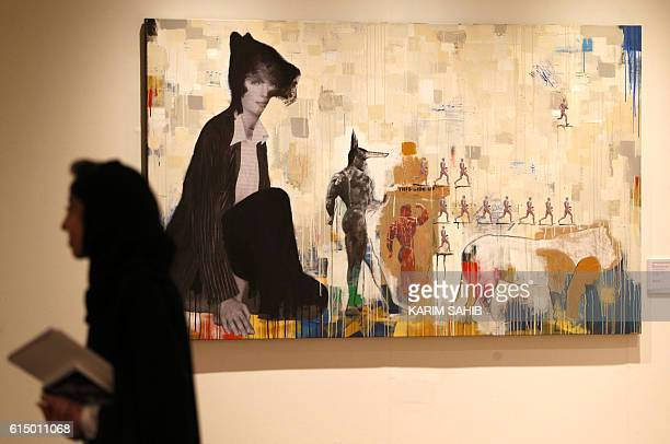 Visitors walks past artwork by Egyptian artist Khaled Hafez displayed at a Christie's exhibition in Dubai on October 16 2016 The works of Saudi...