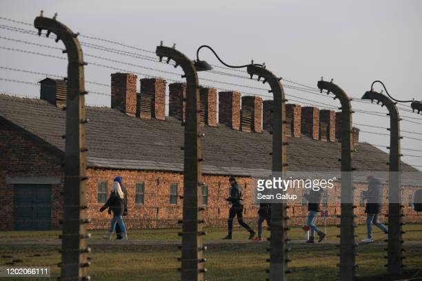 Visitors walks past barbed wire and prisoner barracks at the former Auschwitz-Birkenau German concentration camp on January 26, 2020 near Oswiecim,...