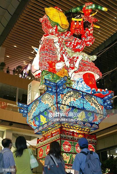 Visitors watch a 20metretall lantern doll 'GoshoGawara TachiNeputa' being displayed at the Tokyo's central shopping mall MaruBiru 22 June 2003 Aomori...