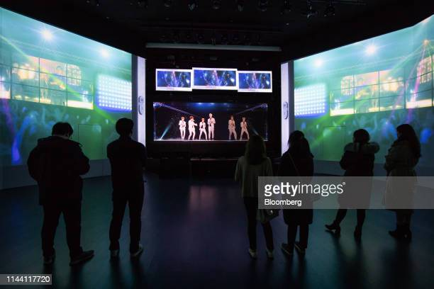 Visitors watch a 3D hologram projection of Kpop singers performing on stage at the KT Corp Klive X VR Park in Seoul South Korea on Tuesday Jan 29...
