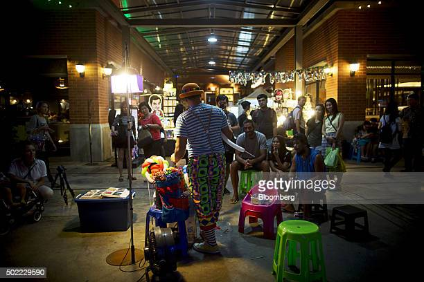 Visitors watch a clown performing with balloons at Asiatique The Riverfront openair mall in Bangkok Thailand on Friday Dec 18 2015 Thai economic...