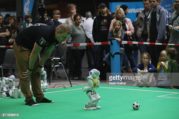 Visitors watch a Nao robot made by Aldebaran Robotics show off its football skills at the Robocup field at the 2016 Berlin Maker Faire on October 1...