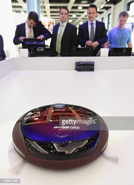 Visitors watch a NaviBot robotic vacuum cleaner in action at the Samsung home appliances stand at the 2010 IFA technology trade fair at Messe Berlin...