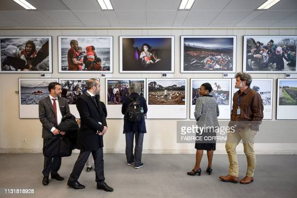 Visitors watch a photography exhibition called 'Making the invisible visible' on recent migration crises by Agence FrancePresse photographers...