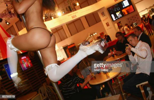 Visitors watch a pole dancer perform at the Venus Erotic Trade Fair during its industry professionals' day on October 16 2008 in Berlin Germany The...