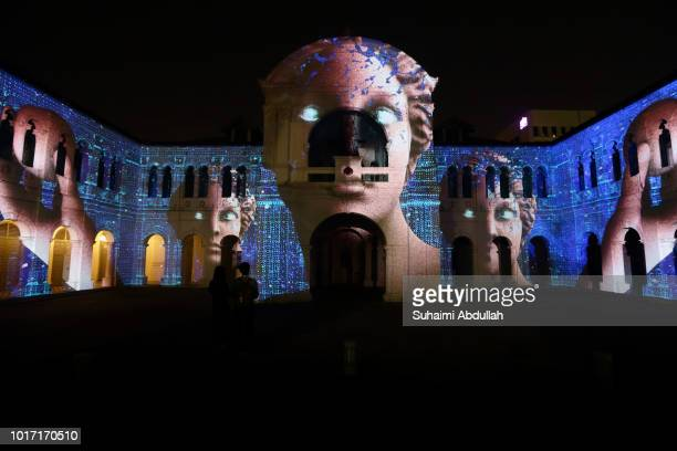 Visitors watch a projection mapping installation on the facade of the Singapore Art Museum titled Odyssey by Arnaud Pottier and Thimothee Mironneau...