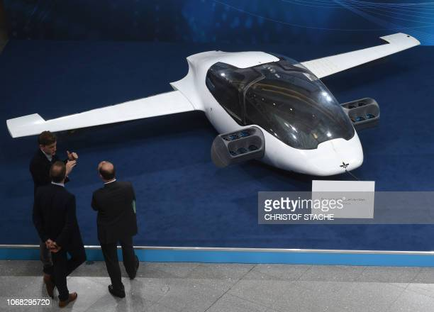Visitors watch a prototyp of the first flying taxi the eVTOL electric vertical takeoff and landing Jet of the company Lilium during the trade fair...