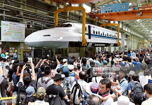 Visitors watch a Shinkansen bullet train hoisted in the air by a crane at Central Japan Railway Co's maintenance plant on July 23 2016 in Hamamatsu...