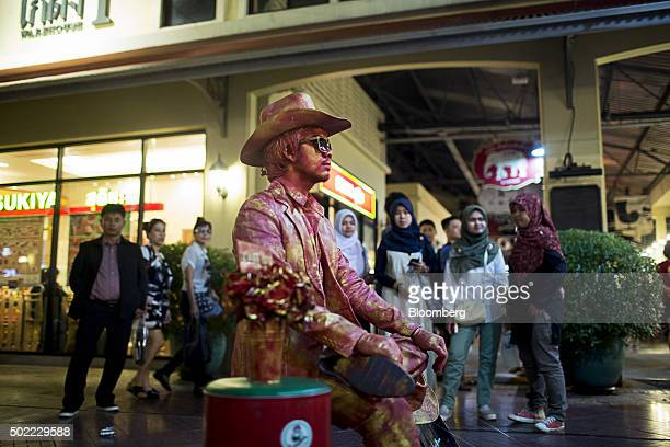 Visitors watch a street performer at Asiatique The Riverfront openair mall in Bangkok Thailand on Friday Dec 18 2015 Thai economic indicators have...