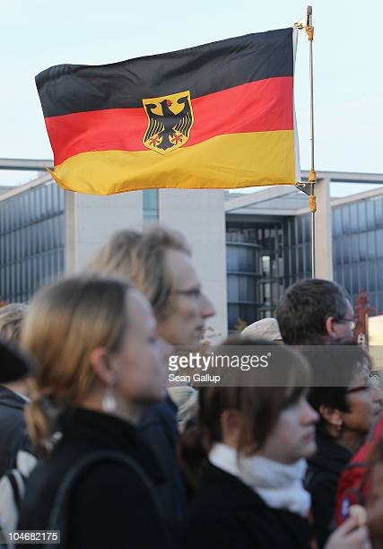 Visitors watch a television documentary on large screen monitors in front of the Reichstag seat of Germany's federal parliament during celebrations...