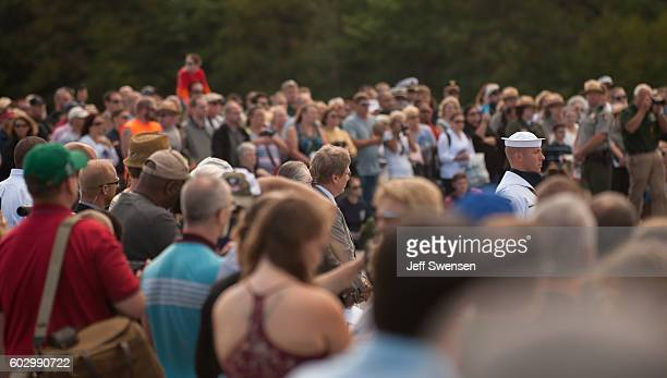Visitors watch a US Navy Ceremonial Honor Guard lay a wreath and present a flag the Wall of Names at the Flight 93 National Memorial on the 15th...