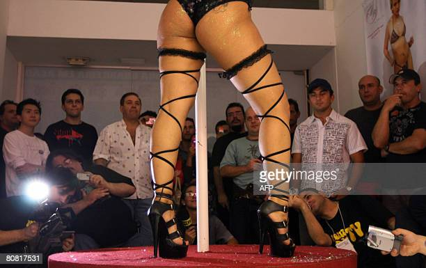 Visitors watch a woman performing poledancing on April 19 2008 during the 12th Erotika Fair Latin America's biggest erotica trade show held at the...