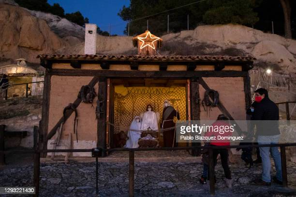 Visitors watch actors Montse, her son Mateo and her husband Javier wear face masks as they perform as the Virgin Mary, an angel and Saint Joseph...