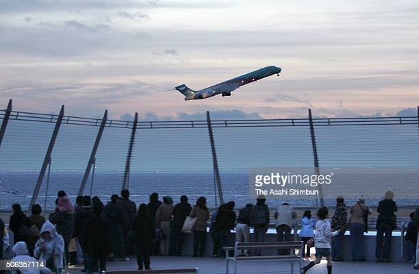 Visitors watch an airplane takes off from the observation deck of the newly opened Chubu International Airport on February 17, 2005 in Tokoname,...