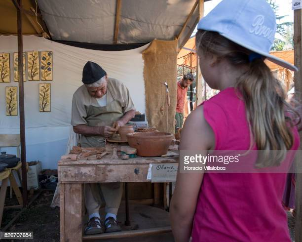 Visitors watch an artisan making clay pottery during the 21st edition of the Medieval Journey dedicated to the kingdom of Afonso IV the Brave King of...