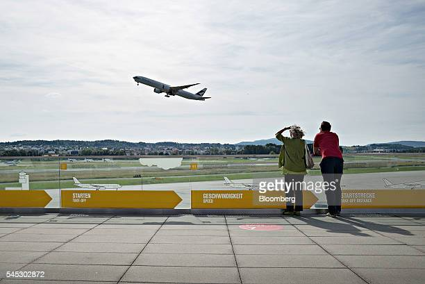 Visitors watch as a passenger aircraft takes off from the runway at Zurich Airport operated by Flughafen Zuerich AG in Zurich Switzerland on...