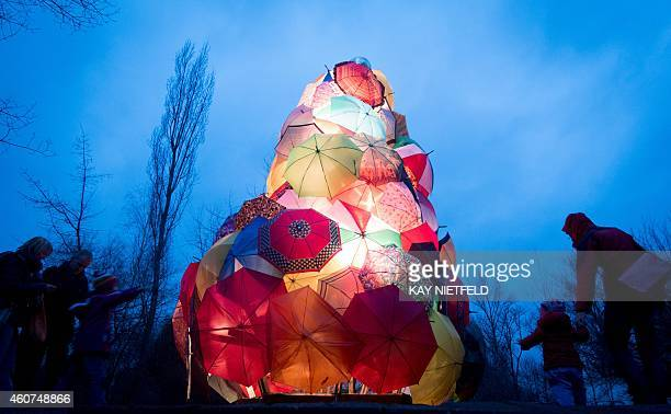 Visitors watch as an installation of umbrellas forming a Christmas tree is illuminated at the Plaenterwald Christmas market in Berlin on December 21...