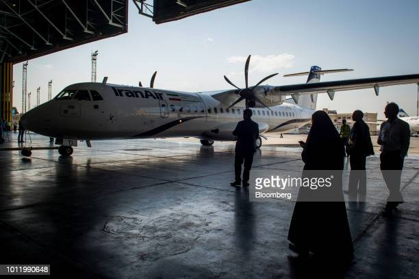 Visitors watch as ground crew position a new twin engine ATR 72600 turboprop aircraft into a hangar after landing at Mehrabad International airport...