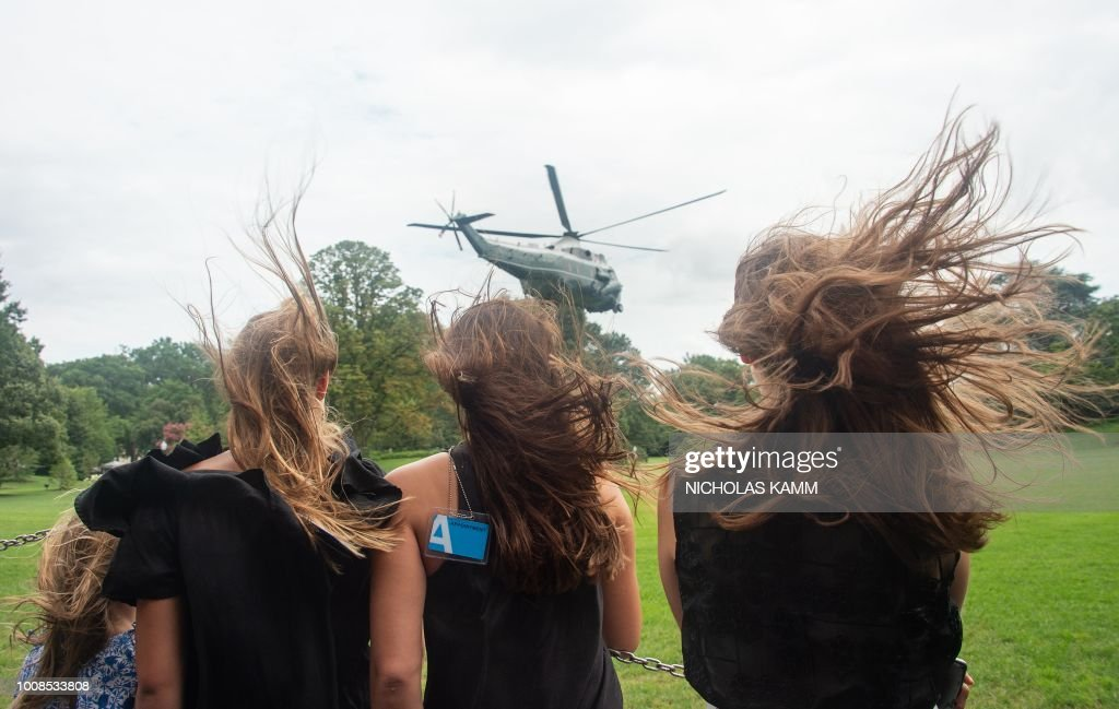 Visitors watch as Marine One carrying US President Donald Trump takes off from the White House in Washington, DC, on July 31, 2018, as he departs for Florida.