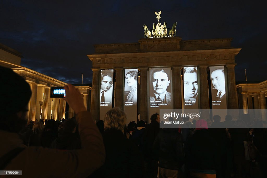 Visitors watch as portraits of Berlin Jewish actors, intellectuals, artists, academics, athletes and others who were persecuted by the Nazis in the 1930s and 40s are projected onto the Brandenburg Gate to commemorate the 75th anniversary of the Kristallnacht pogroms on November 10, 2013 in Berlin, Germany. Events are taking place across the country to commemorate the day in 1938 when Nazi gangs across Germany and Austria burned down over 1,000 synagogues, smashed Jewish-owned businesses, looted Jewish residences and killed several hundred Jews. Anti-Semitism was a central component of Adolf Hitler's rise to power and won him wide-spread sympathy among ordinary Germans and Austrians.