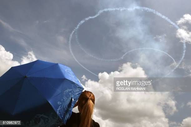 TOPSHOT Visitors watch as South Korea's aerobatics team Black Eagles flying KAI T50B aircraft create a yin and yang logo as they perform an aerial...