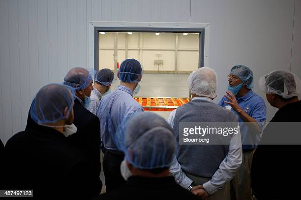 Visitors watch as White Castle hamburger Sliders are produced at the new White Castle Co Distributing Plant in Vandalia Ohio US on Wednesday April 30...