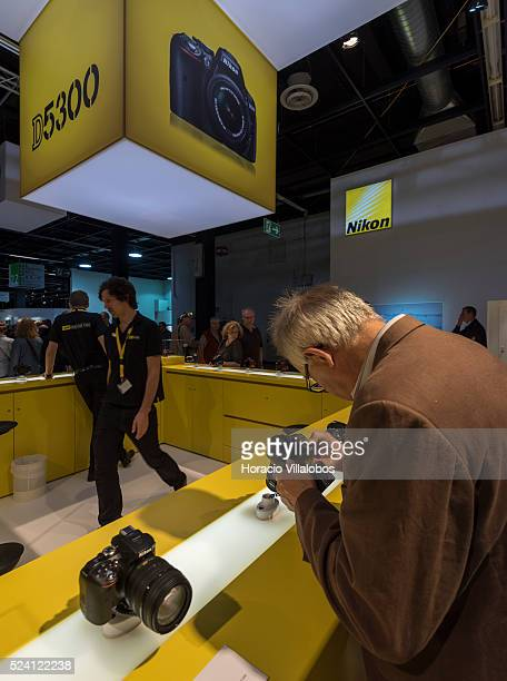 Visitors watch cameras at Nikon stand in Photokina 2014 in Cologne Germany 18 September 2014 Photokina the world's leading imaging fair brings...