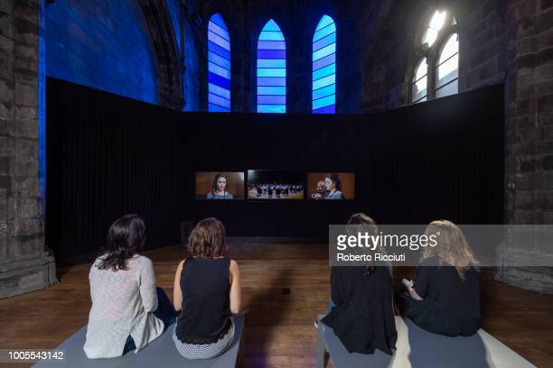 Visitors watch film installation 'Tryptic' by artists Ross Birrell and David Harding on the first day of the 2018 Edinburgh Art Festival at Trinity...